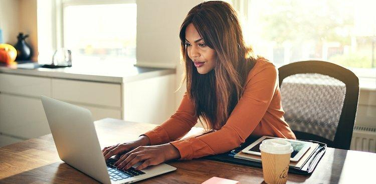 A women sitting at dinning table and working in laptop
